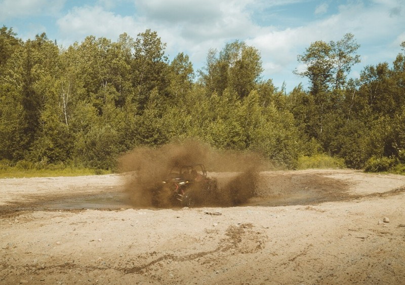 guest-driving-a-Polaris-RZR-through-a-muddy-patch-along-the-trail