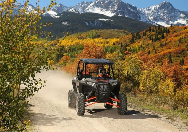 guest-driving-a-Polaris-RZR-down-a-dirt-trail-surrounded-by-mountains1