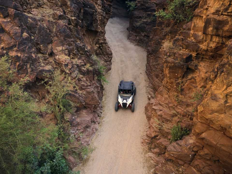 aerial view of off-road vehicle driving through slot canyon