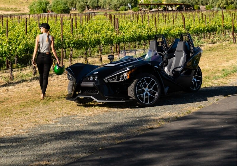 guest overlooking the winery walking towards a parked Polaris Slingshot