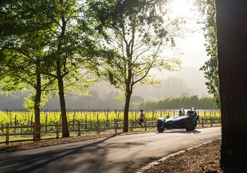 guest sitting along a fence while overlooking a winery next to a parked three wheeled vehicle