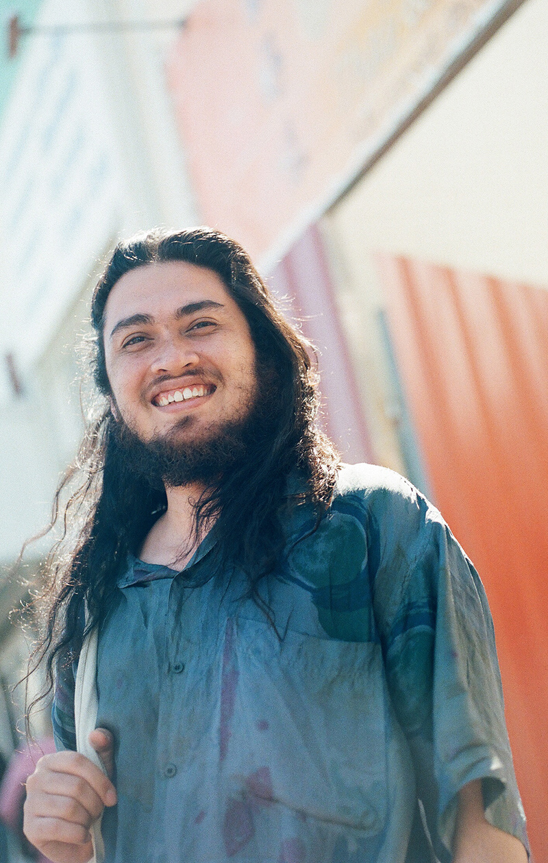 An artist with long hair smiles at the camera