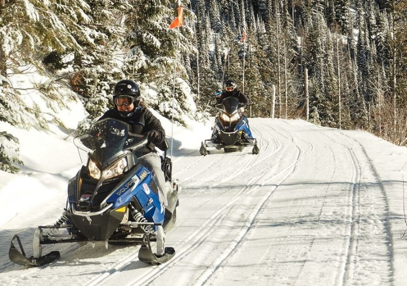 guests driving a snowmobiles along mountainside