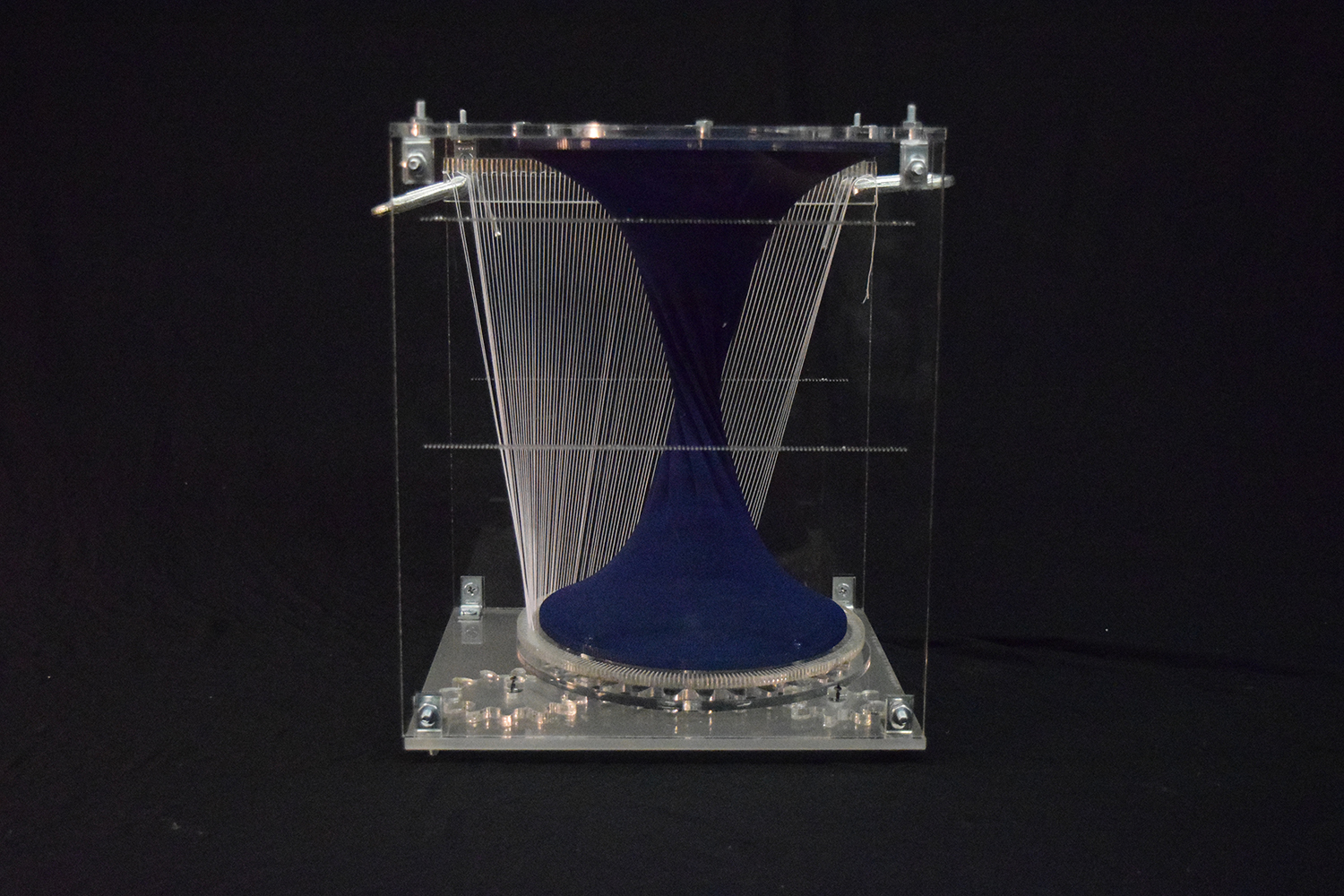 acrylic box holding navy textile form and band of strings inside