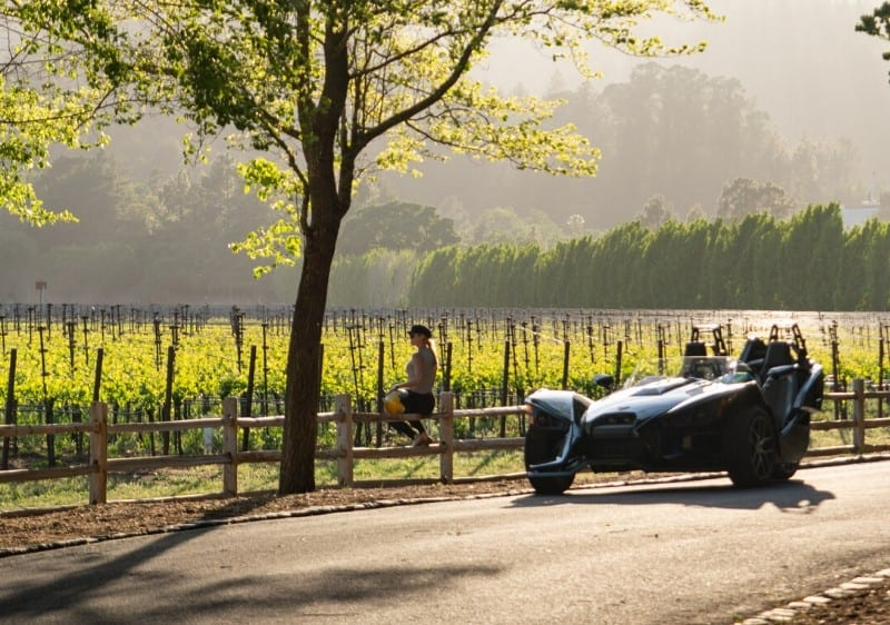 guest sitting along a fence while overlooking a winery next to a parked Polaris Slingshot