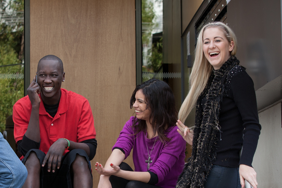 This is a photo of three young people sitting outside laughing and smiling.