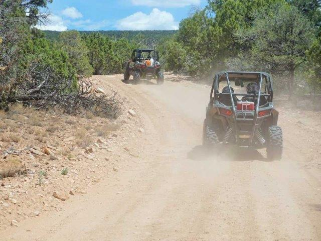 off-road vehicles driving down a dirt road