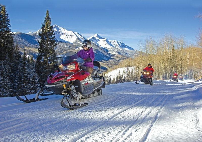 guets riding snowmobiles near scenic San Juan Mountains