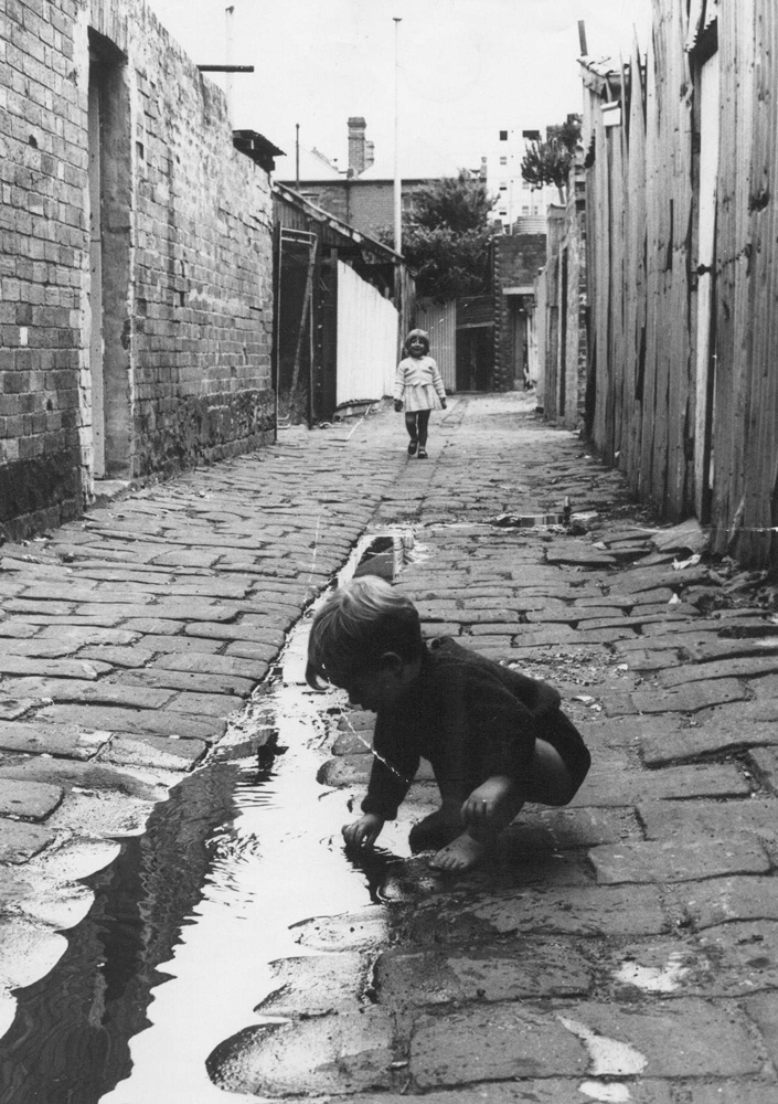 This is a black and white photo of a young boy playing in a puddle in a Fitzroy laneway.