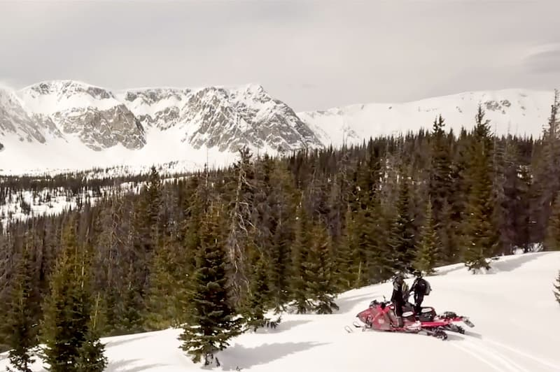 guests on Snowmobiles looking over Wyoming mountains