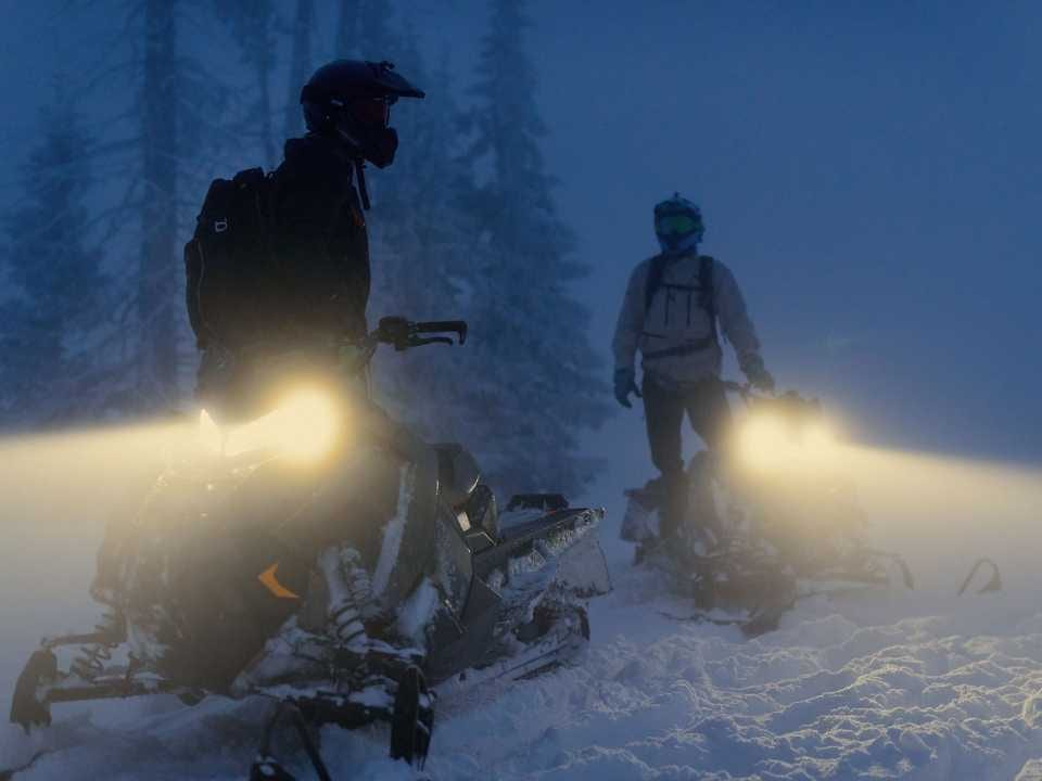 snowmobile lights shining at dusk