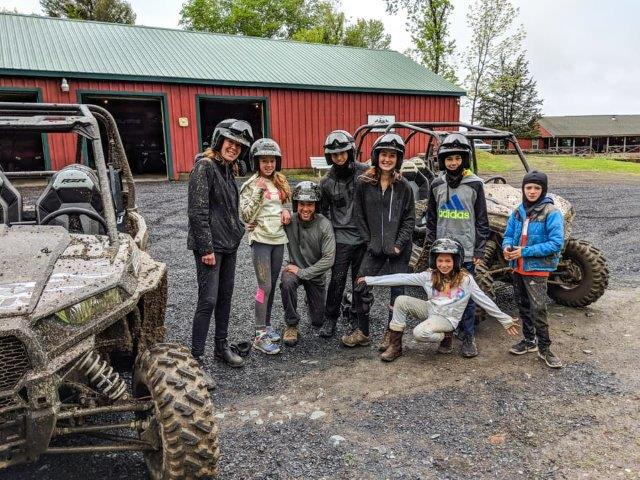guests in helmets smiling by off-road vehicles