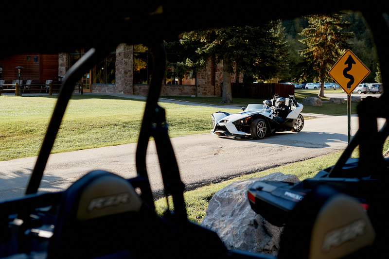 A-view-of-a-Polaris-Slingshot-from-behind-a-RZR