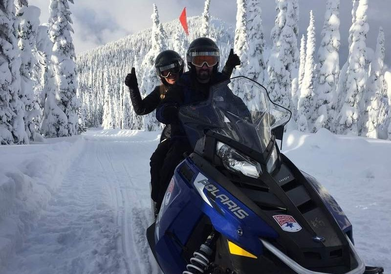 guests on a snowmobile through snow covered trees