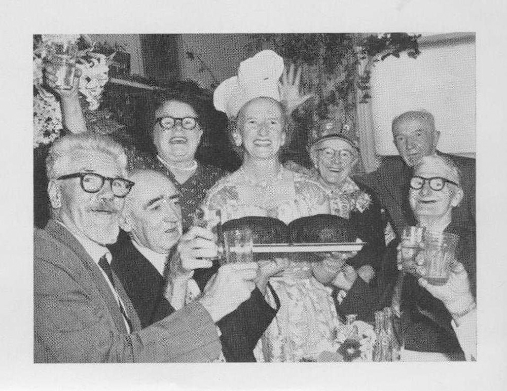 This is an image of Aged Care officer Jess Millot serving Christmas pudding for Coolibah Club members at Christmas time. They are happy and joyful in this black and white photograph.