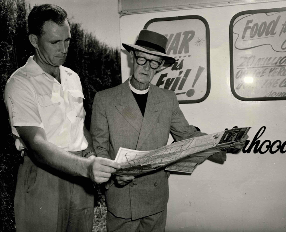 This is a photo of Neville Brooke and Father Tucker on the Food for Peace campaign trail. They are standing together looking at a large document.