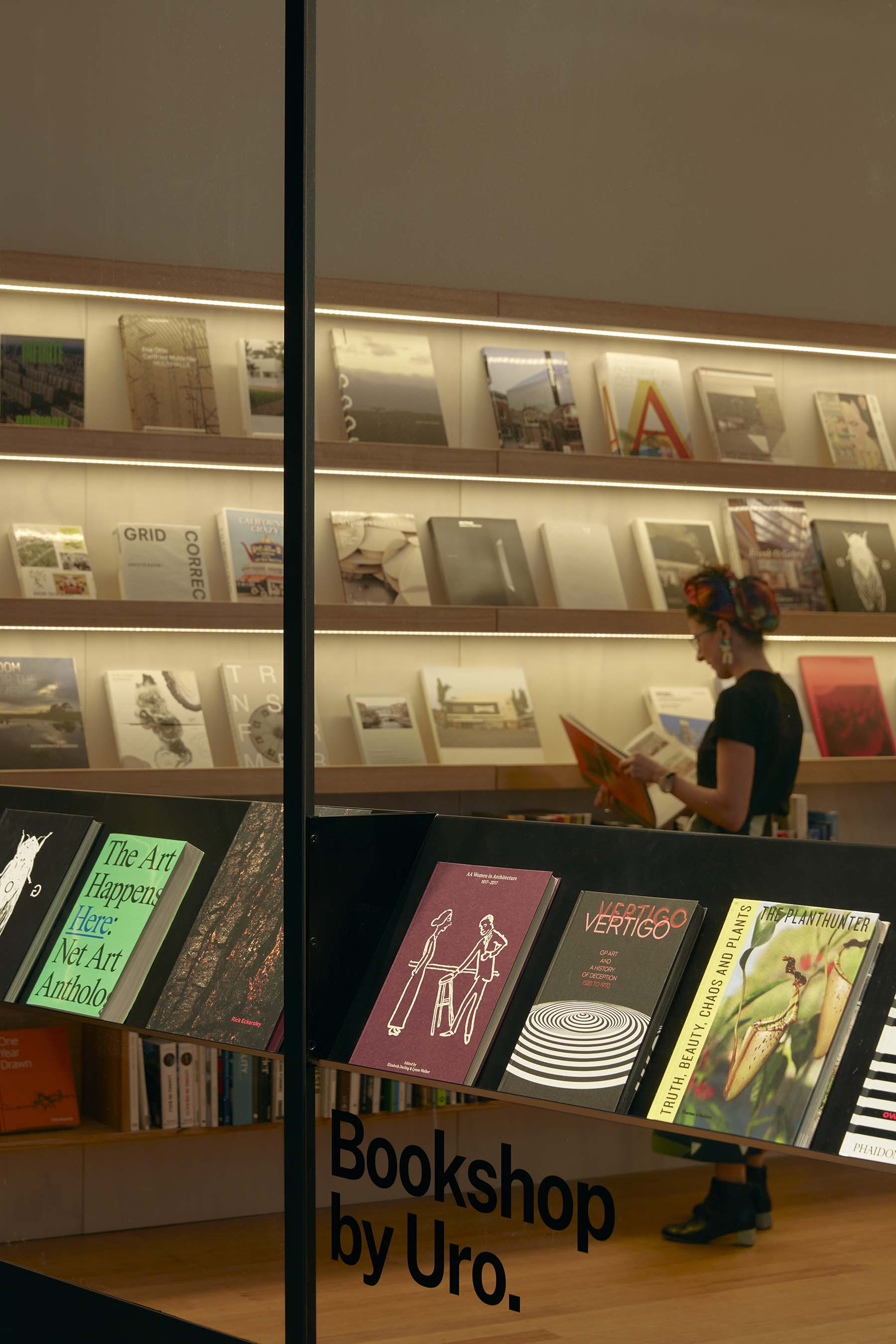 The window of Bookshop by Uro. Walls and shelves of books are visible, and a person is browsing the books available.