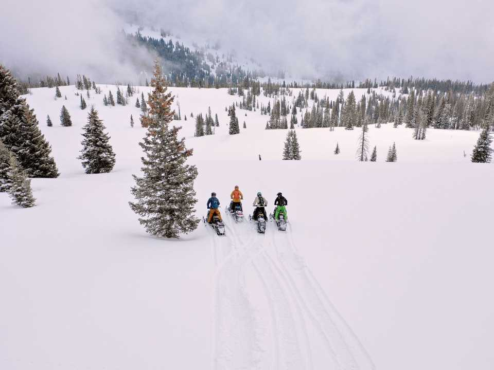 group of snowmobilers driving in mountians