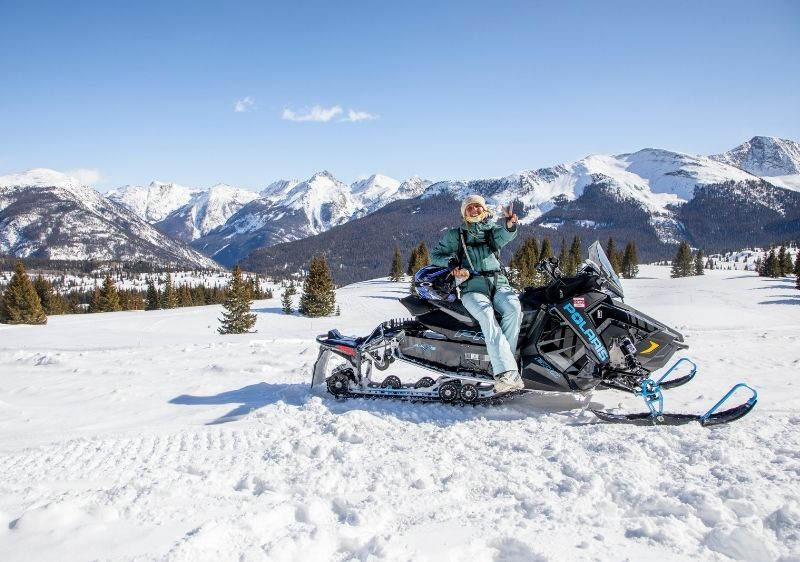 guest on snowmobile surrounded by San Juan Mountains