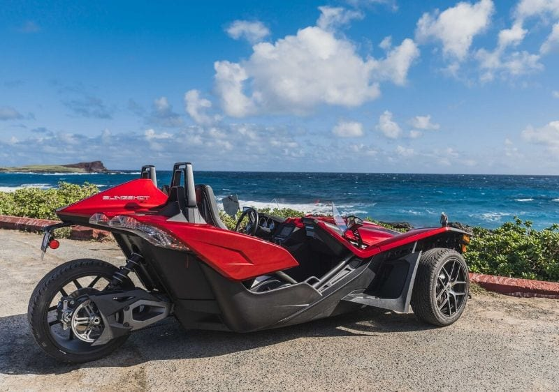 Polaris Slingshots parked at a coastal lookout of the ocean