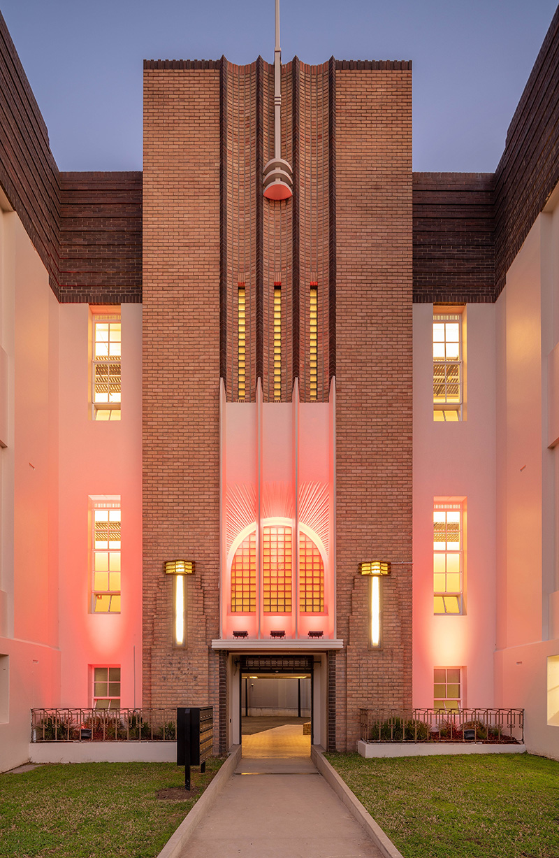 The art Dudok facade of the Johnston Street Building, lit up by warm pink lights