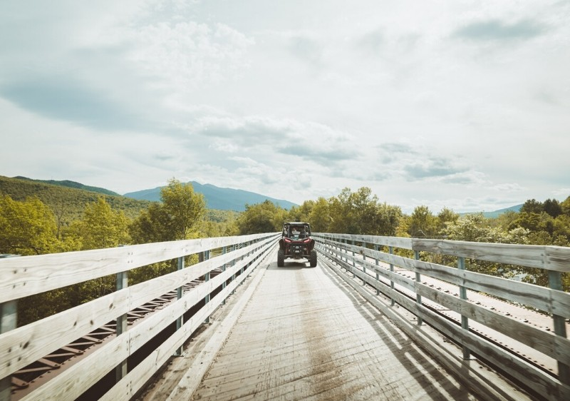 guest-driving-a-Polaris-RZR-across-a-bridge-overlooking-the-Appalachian-mountains