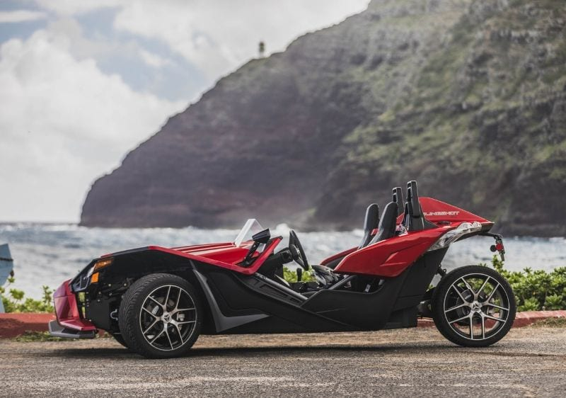 Polaris Slingshots parked along the coast in front of a scenic mountain range