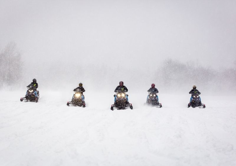 group of snowmobilers driving on open trails2