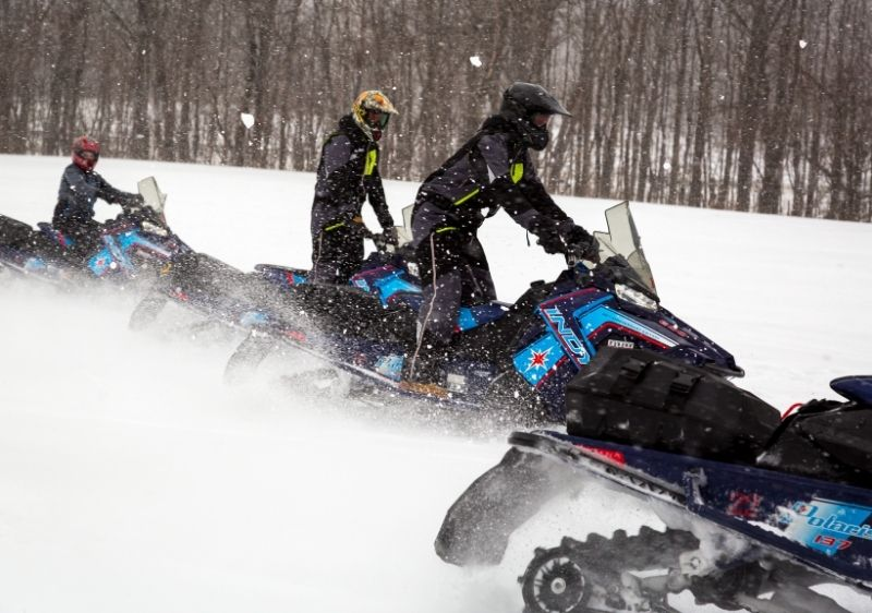 group of snowmobilers driving on open trails