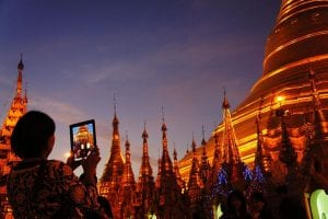 Shwedagon Pagoda glows a dark orange as the gold is lit up against the dark sky
