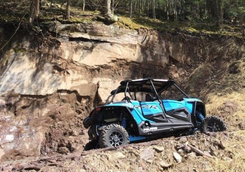 Polaris-RZR-parked-on-a-rocky-mountain-road-near-a-cliff