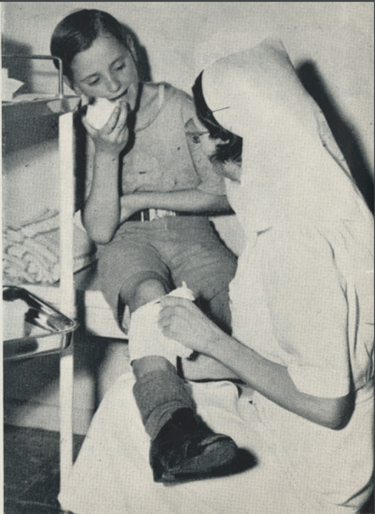 This is a photo of a nurse helping a child at the Children's Health Clinic in 1952