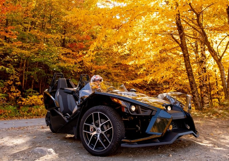 guest-riding-in-a-Polaris-Slingshot-driving-through-trees-surrounded-by-fall-colors