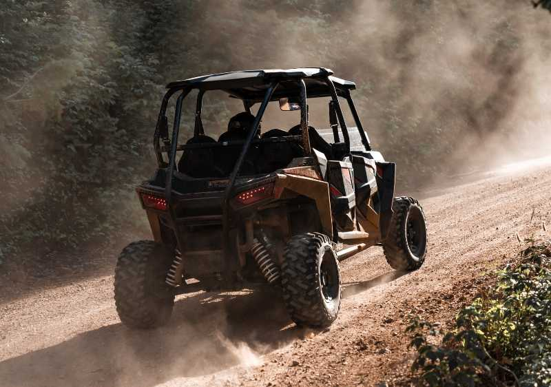off-road vehicle on a dusty dirt trail