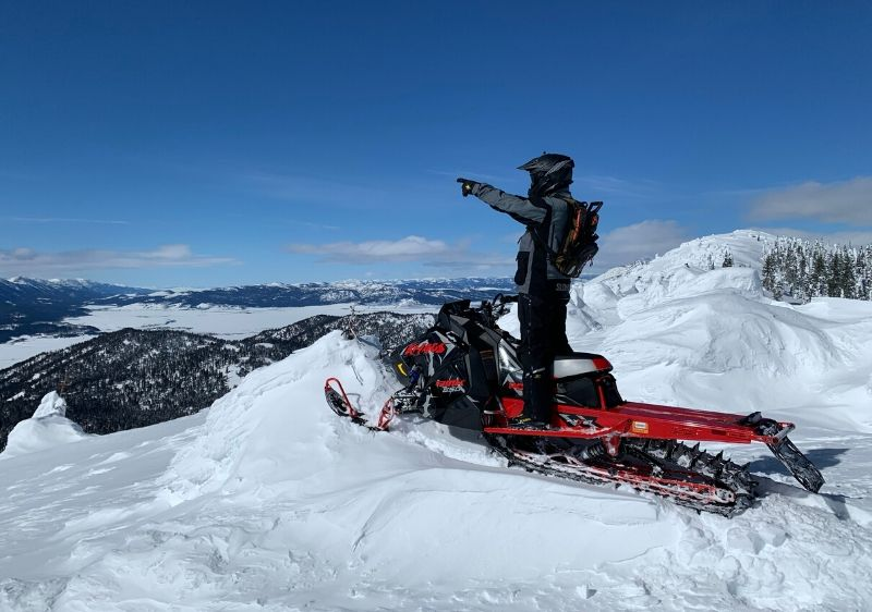 guest-on-a-Polaris-Snowmobile-pointing-at-the-scenic-mountain-range