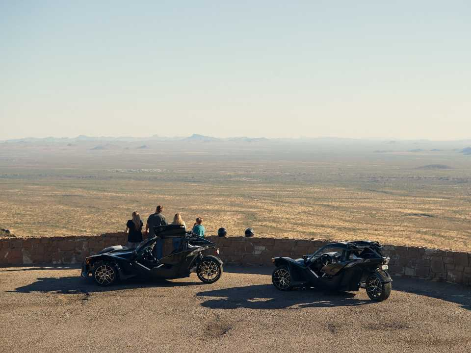 family overlooking scenic desert view with Polaris Slingshots