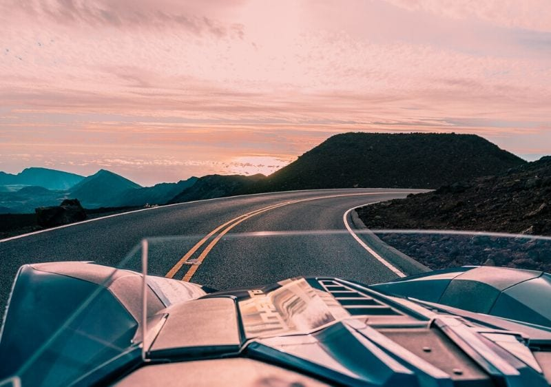 guest driving a Polaris Slingshot driving into the sunset