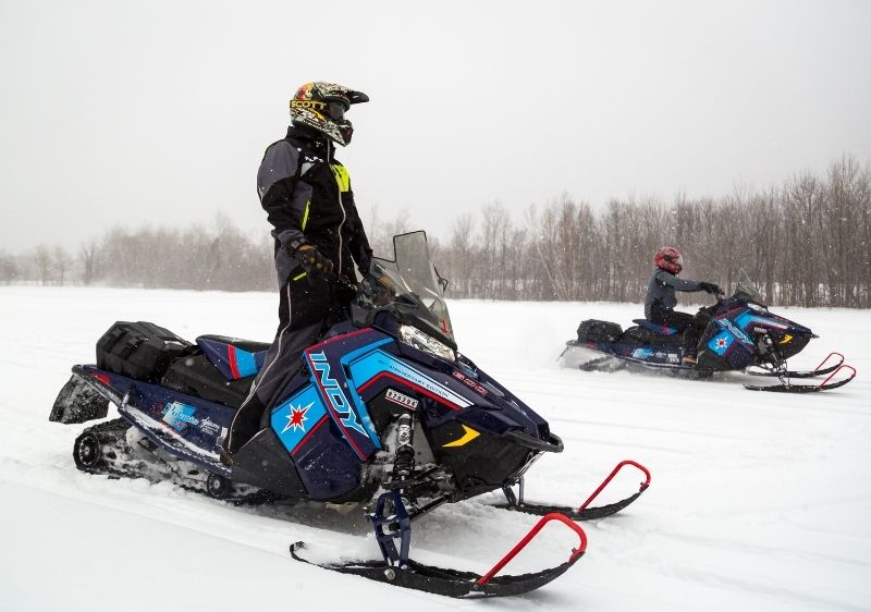 snowmobilers driving through open field
