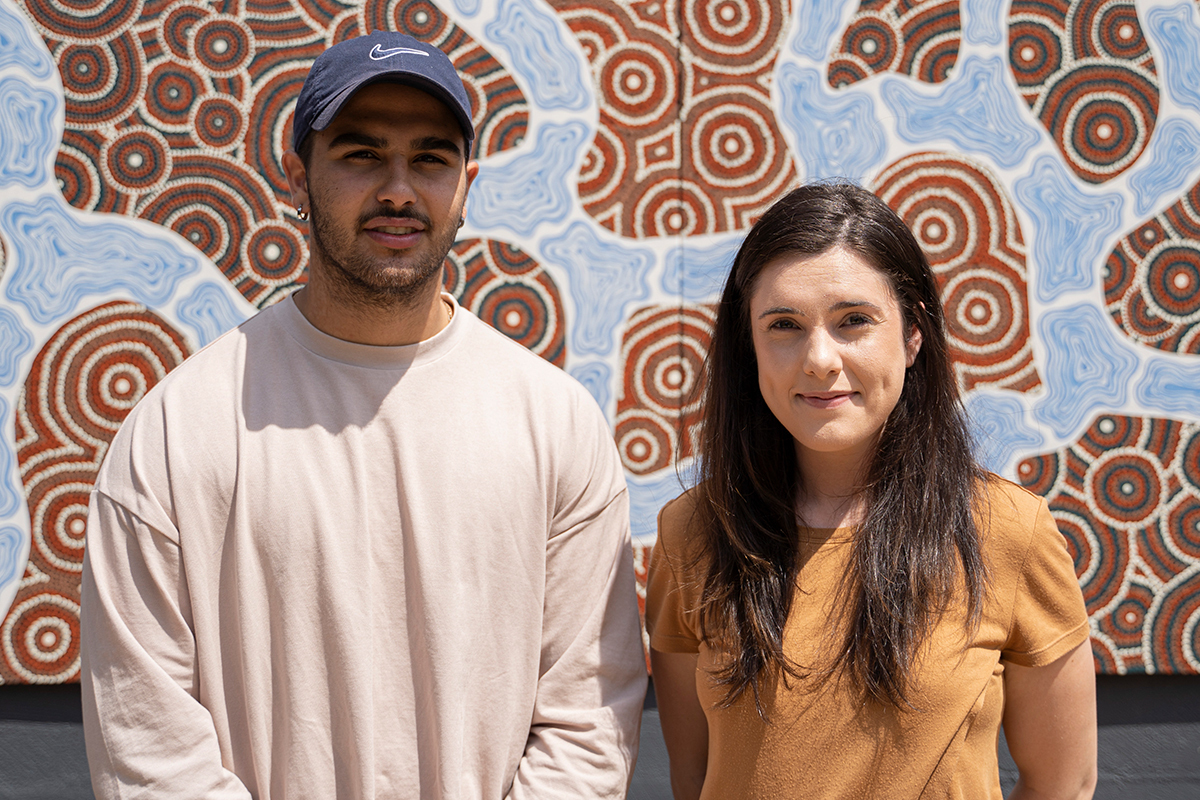 This is a photo of CareerTrackers interns Stephany and Jamarl undertook internships with our youth programs. They are smiling and the camera and are standing in front of Aboriginal artwork.