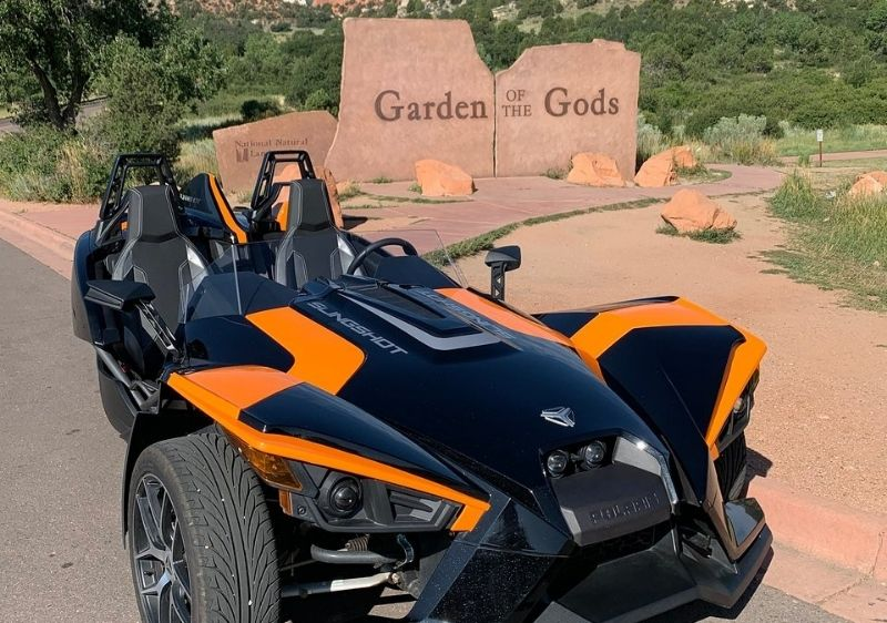 three wheeled vehicle parked by Garden of the Gods sign