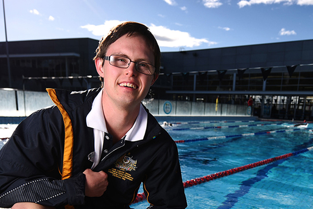 This is a photo of an NDIS Participant standing with his bag and smiling at the camera. He is in front of a pool.