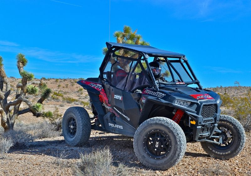 guests-in-a-parked-Polaris-RZR-in-the-middle-of-the-desert