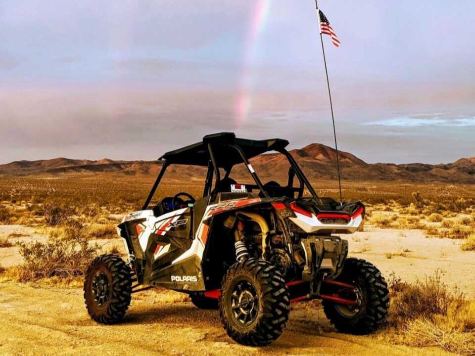 off road vehicle under a rainbow in the desert