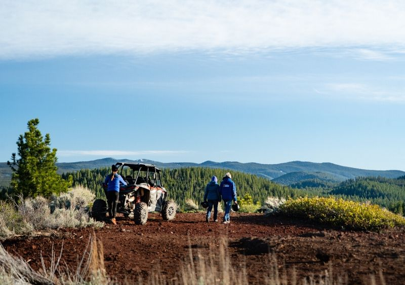 guests-overlooking-the-scenic-mountainous-view-of-Oregon-next-to-a-parked-Polaris-RZR