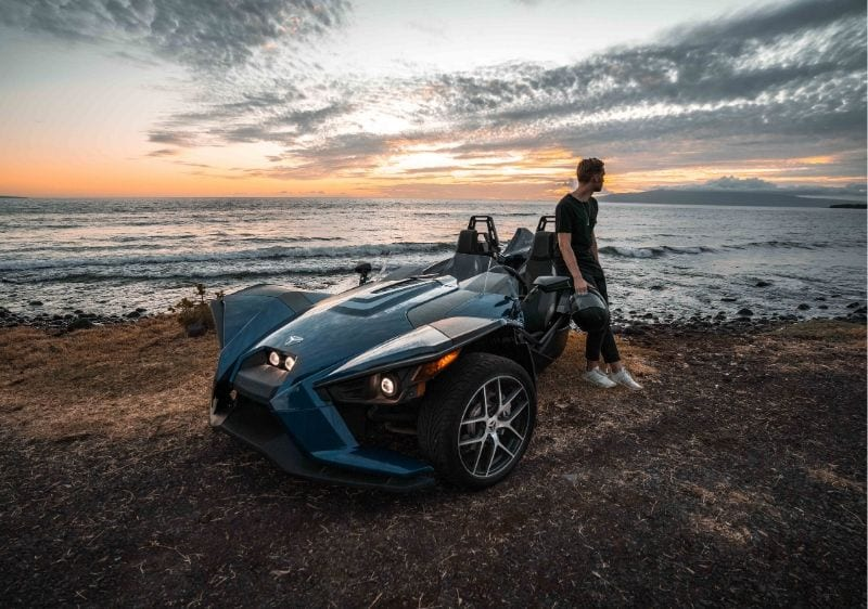 guest standing by a Polaris Slingshot at sunset