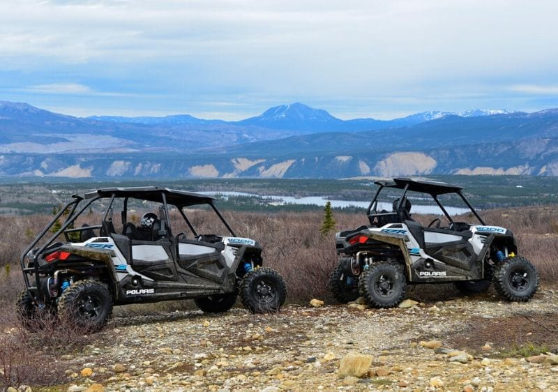 guests in off-road vehicles looking a the scenic mountain range