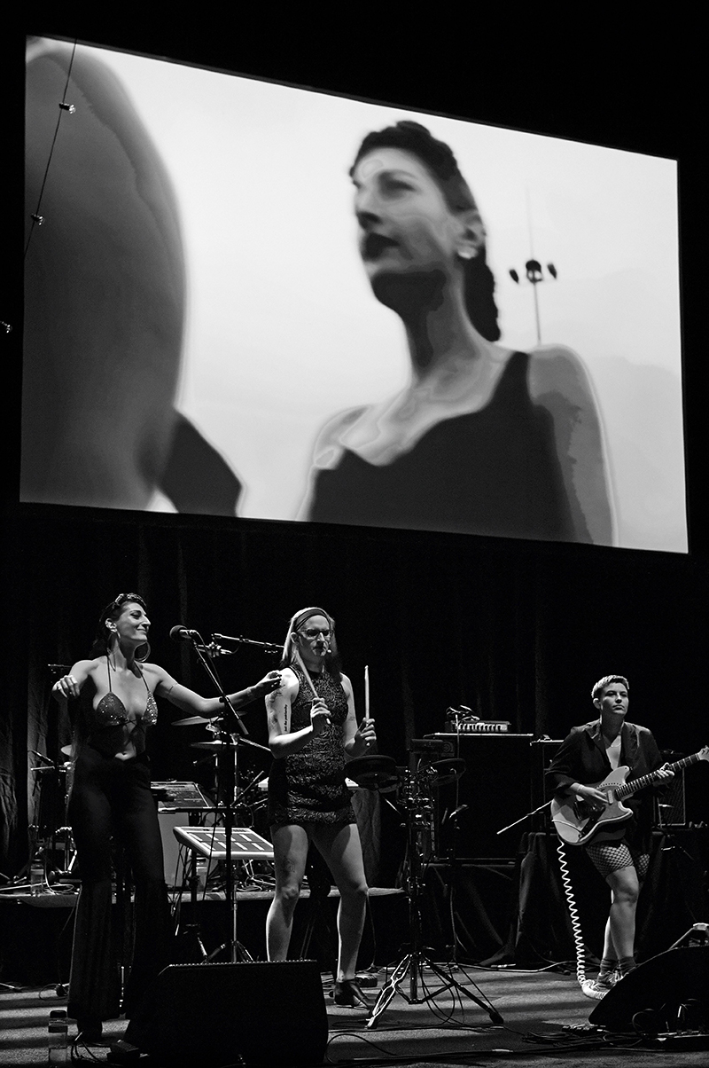 Black and white image of a trio of performers on a stage