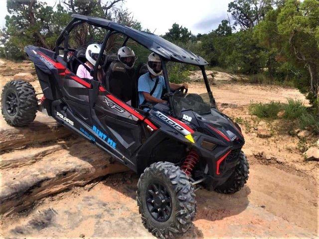 guests in an off-road vehicle drving over rocky terrain