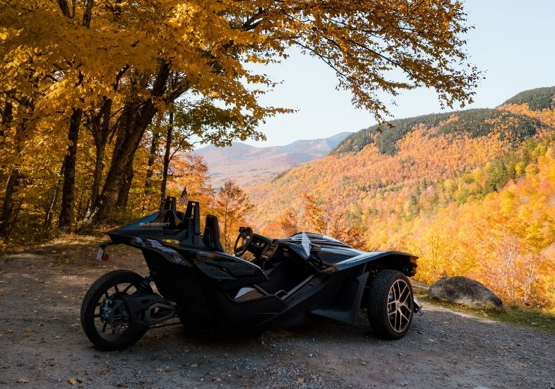 guest-riding-in-a-Polaris-Slingshot-driving-through-trees-surrounded-by-fall-colors1