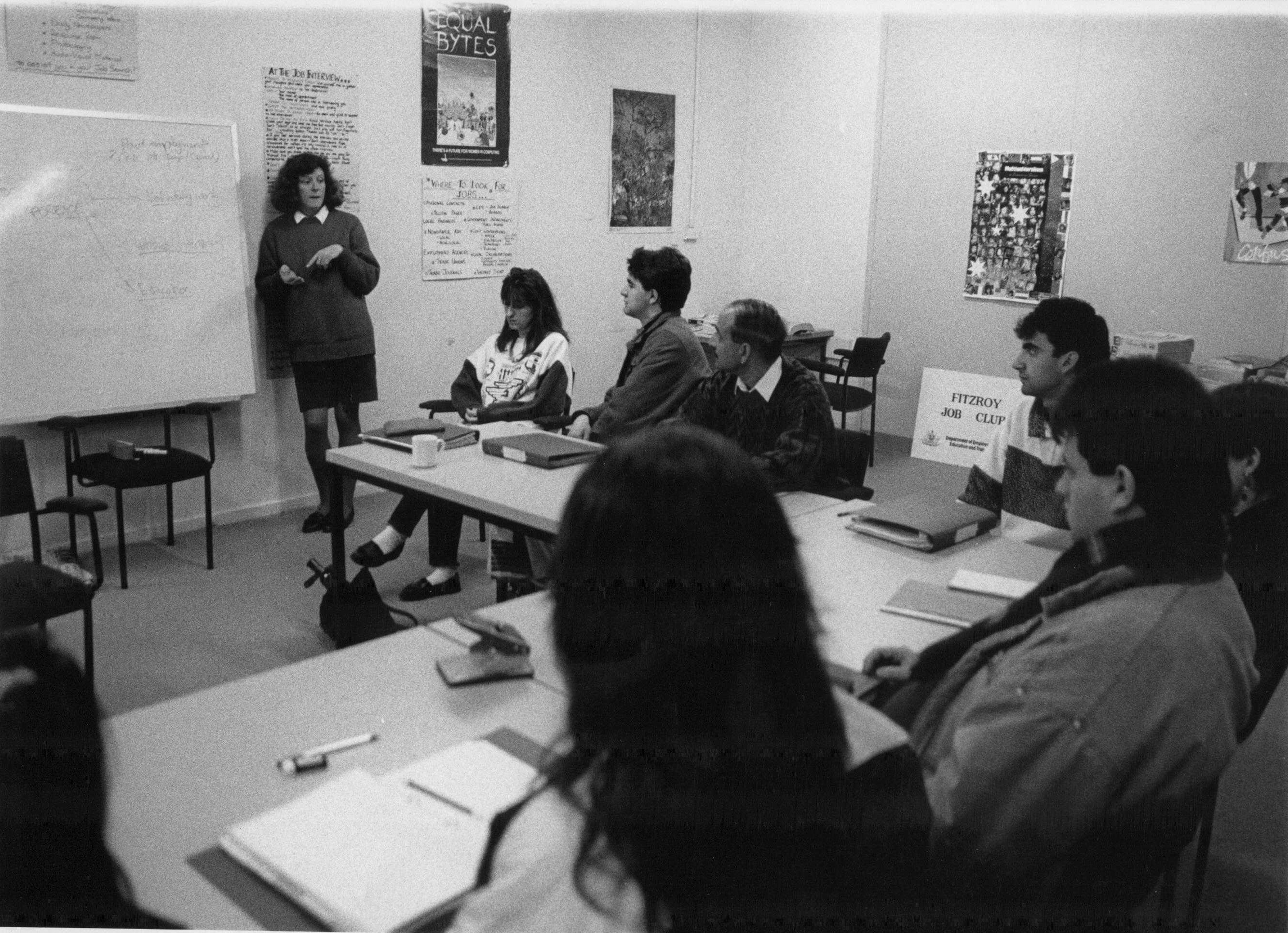 This is a black and white photo of an employment officer teaching job seekers. There are about 10 people listening to the employment officer. She is standing in front of a whiteboard.